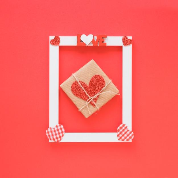 Presente vicino alla cornice con i simboli del titolo e del cuore dell'amore Foto Gratuite
