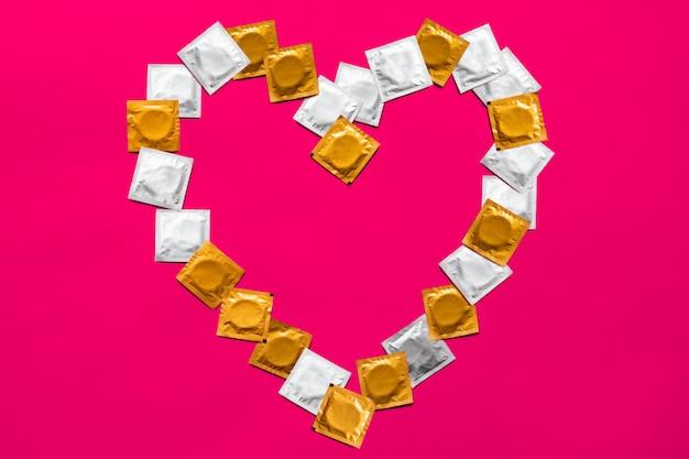 Preservativi a forma di cuore, vista dall'alto. grandi quantità di preservativi, sparati dall'alto - sesso sicuro e concetto di contraccezione Foto Premium