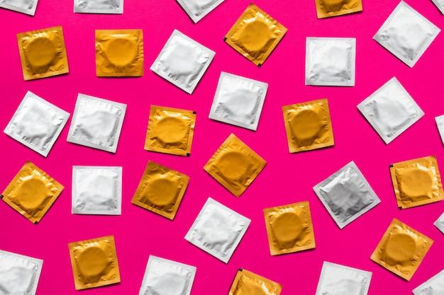 Preservativi in superficie rosa, vista dall'alto. grandi quantità di preservativi, sparati dall'alto - sesso sicuro e concetto di contraccezione Foto Premium