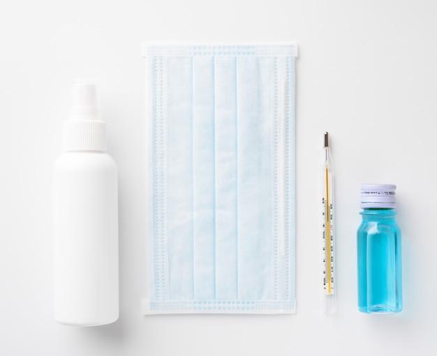 Prevenzione del coronavirus con mascherina chirurgica medica, disinfettante per le mani, gel per alcool e termometro, vista dall'alto Foto Premium