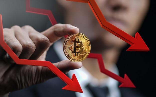 Prezzo bitcoin in calo. freccia rossa 3d di holding bitcoin with dell'uomo d'affari giù Foto Premium