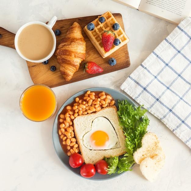 Prima colazione inglese completa con uova fritte, fagioli, toast, insalata, pomodori su bianco Foto Premium