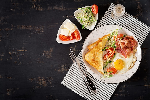 Prima colazione inglese - toast, uova, pancetta e pomodori e insalata di microgreens. vista dall'alto. distesi Foto Premium