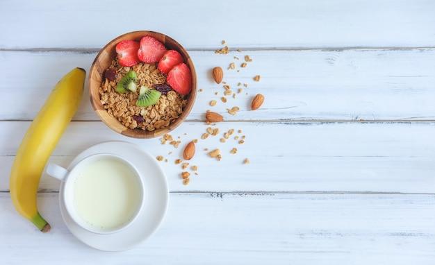 Prima colazione sana, cereali muesli con latte e banana Foto Premium