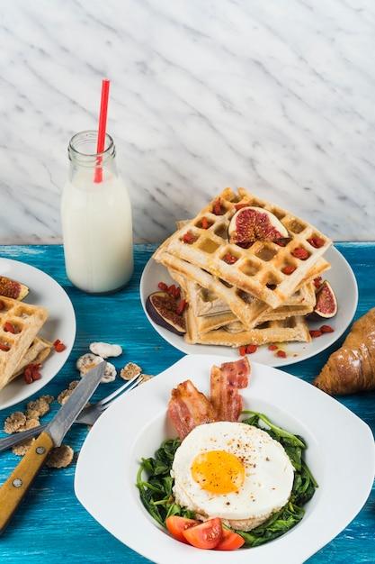 Prima colazione sana con la bottiglia per il latte sulla tavola di legno contro il contesto strutturato di marmo Foto Gratuite