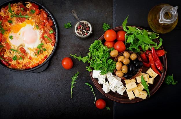 Prima colazione. uova fritte con verdure. shakshuka in una padella su un nero in stile turco. Foto Gratuite