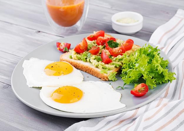 Prima colazione. uovo fritto, insalata di verdure e un panino alla griglia con avocado Foto Premium
