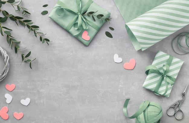 Primavera piatta distesa con scatole regalo, cuori e foglie di eucalipto Foto Premium