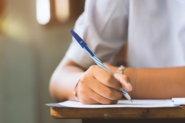 Primo piano a disposizione della penna di tenuta dello studente e l'esame in aula con lo stress per il test di educazione. Foto Premium