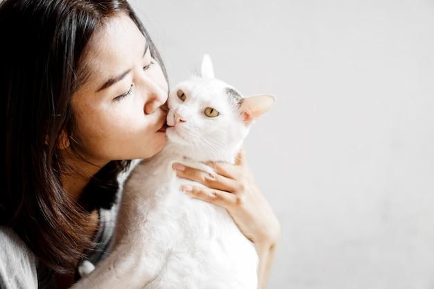 Primo piano bianco sveglio baciante del gatto della donna asiatica Foto Premium