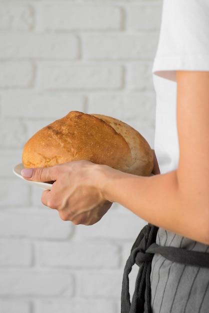Primo piano che tiene pane rotondo fresco Foto Gratuite