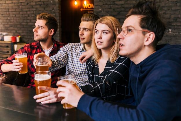 Primo piano degli amici che tengono i vetri di birra che osservano via Foto Gratuite