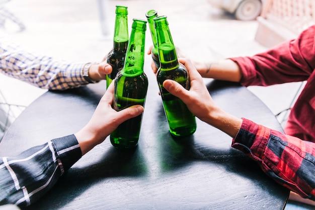 Primo piano degli amici che tengono le bottiglie di birra sopra la tavola di legno Foto Gratuite
