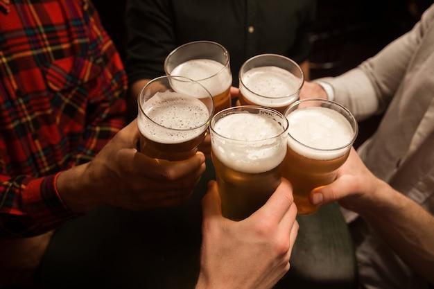 Primo piano degli uomini che tostano con la birra Foto Gratuite