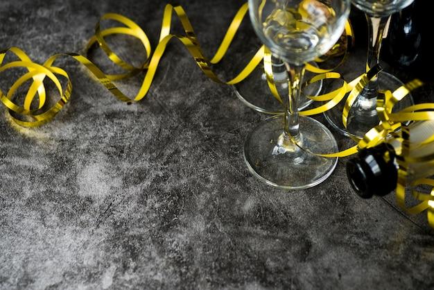 Primo piano dei bicchieri di vino e della bottiglia vuoti trasparenti con le fiamme dorate sopra fondo strutturato Foto Gratuite