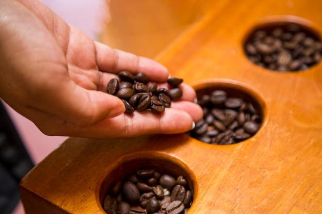 Primo piano dei chicchi di caffè femminili della tenuta della mano Foto Gratuite