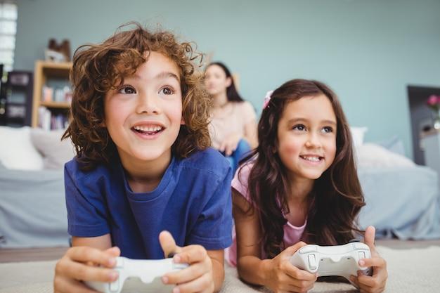 Primo piano dei fratelli felici con i controller che giocano video gioco Foto Premium
