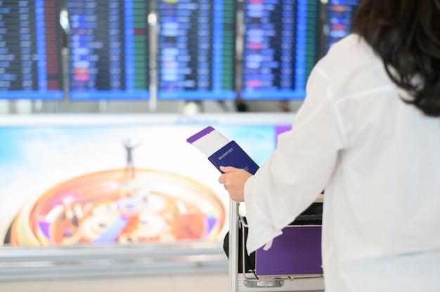 Primo piano dei passaporti della holding della ragazza e della carta d'imbarco all'aeroporto Foto Premium