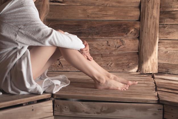 Primo piano dei piedi della donna sul banco di legno a sauna