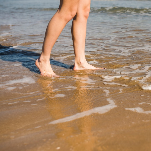 Primo piano dei piedi nudi della donna sulla spiaggia Foto Gratuite