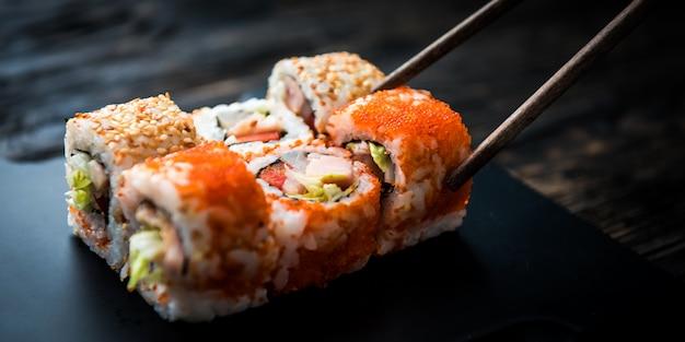 Primo piano dei rotoli di sushi con le bacchette Foto Premium