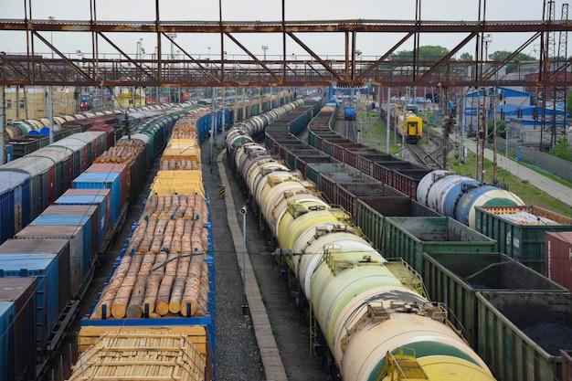 Primo piano dei treni merci. vista aerea dei treni sulla stazione ferroviaria. carri con legno e olio. autunno Foto Premium