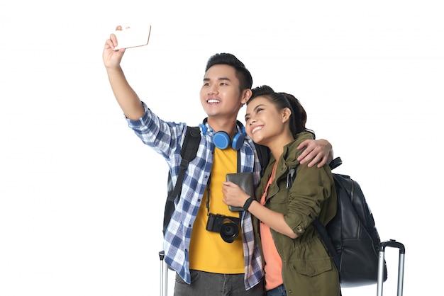 Primo piano dei turisti asiatici che prendono un selfie contro il fondo bianco Foto Gratuite