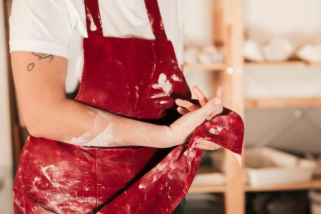 Primo piano dei vasai femminili che puliscono le sue mani con il grembiule rosso Foto Gratuite