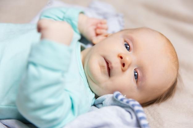 Primo piano del bambino dolce calmo che si trova sulla coperta Foto Gratuite