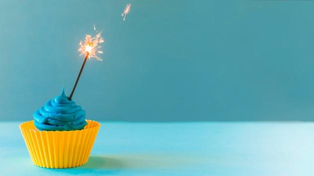 Primo piano del bigné con lo sparkler illuminato su priorità bassa blu Foto Gratuite