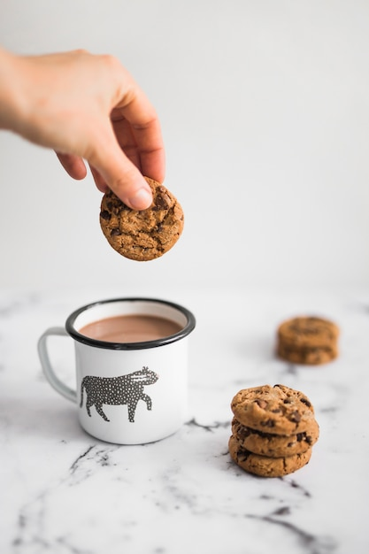 Primo piano del biscotto della holding della mano sopra la tazza di tè sul contesto di marmo Foto Gratuite