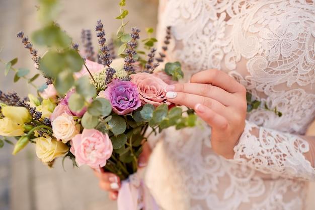 Primo piano del bouquet da sposa rosa e viola nelle mani della sposa Foto Gratuite