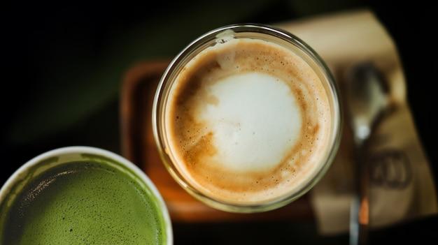 Primo piano del caffè caldo latte e tè verde di matcha in tazza sulla tavola. vista dall'alto. scena di bar o ristorante Foto Premium