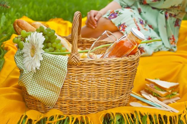 Primo piano del cestino da picnic con cibo, frutta, bicchieri da vino, fiore sulla copertina gialla Foto Premium