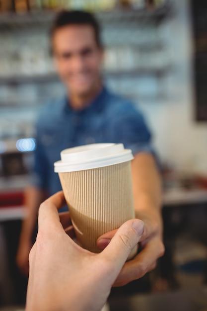 Primo piano del cliente che prende caffè dal barista al caffè Foto Premium