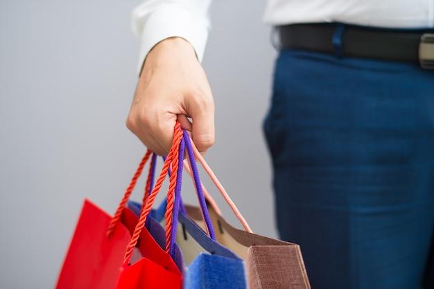 Primo piano del compratore che tiene i sacchetti della spesa Foto Gratuite
