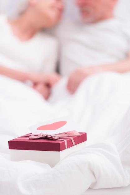 Primo piano del contenitore di regalo con la cartolina d'auguri sulla coperta bianca Foto Gratuite