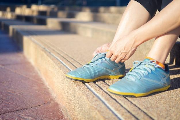 Primo piano del corridore femminile di forma fisica di sport che si prepara per pareggiare all'aperto. Foto Premium