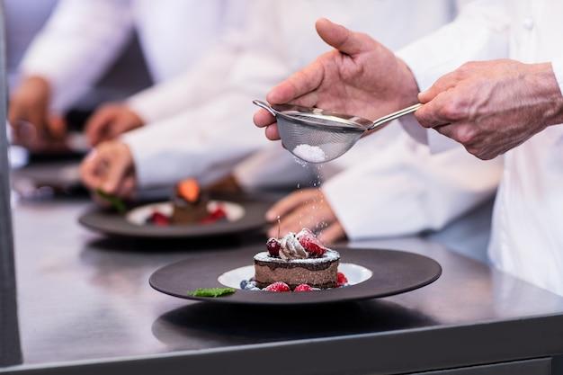 Primo piano del cuoco unico che finisce un piatto di dessert Foto Premium