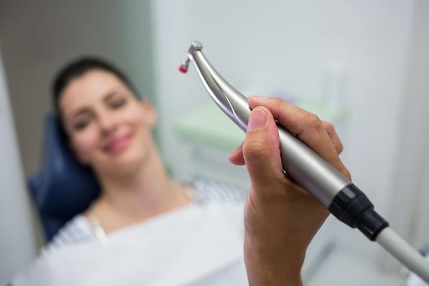 Primo piano del dentista che tiene un odontoiatria, manipolo dentale mentre esaminando una donna Foto Gratuite