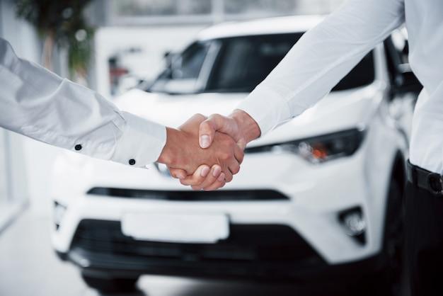 Primo piano del direttore delle vendite in abito nero che vende l'auto al cliente Foto Gratuite