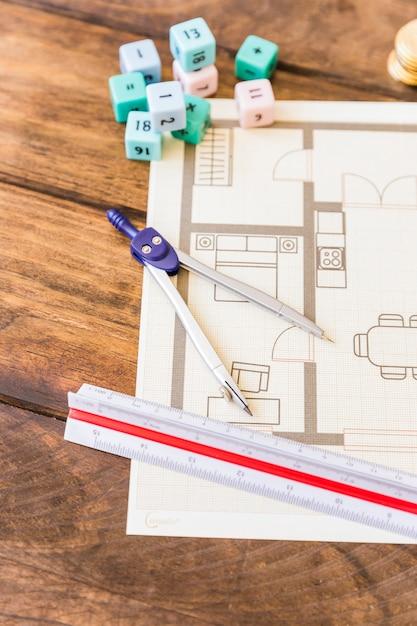 Primo piano del divisore, del righello, dei blocchi per la matematica e del modello sullo scrittorio di legno Foto Gratuite