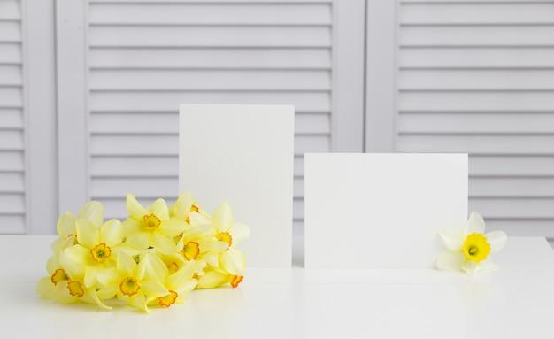 Primo piano del fiore giallo del narciso nel vaso sopra gli otturatori bianchi Foto Gratuite