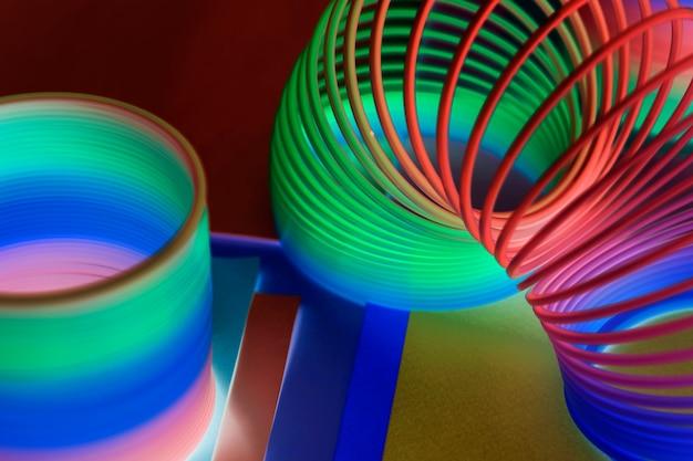 Primo piano del fondo del giocattolo della molla dell'arcobaleno in un effetto negativo Foto Gratuite