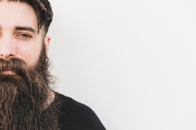 Primo piano del giovane barbuto che guarda l'obbiettivo su sfondo bianco Foto Gratuite