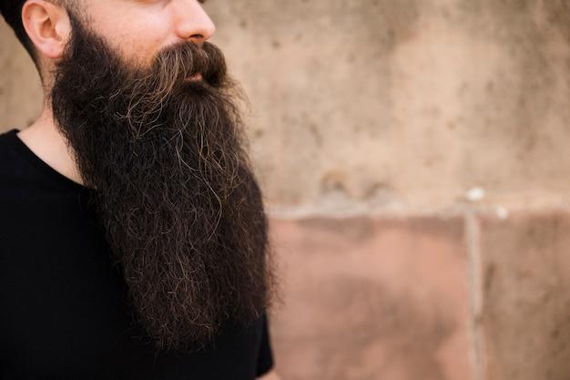 Primo piano del giovane barbuto contro il muro Foto Gratuite