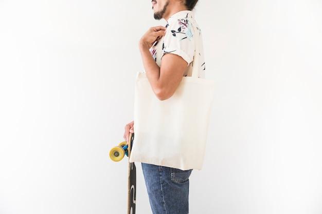 Primo piano del giovane con la borsa della totalizzatore che tiene pattino Foto Gratuite