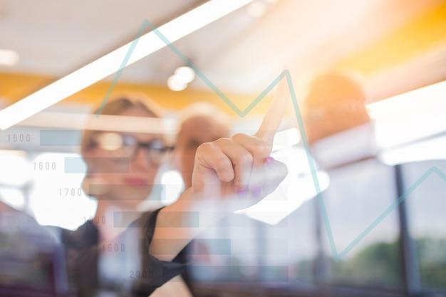 Primo piano del grafico commovente della donna di affari sullo schermo virtuale Foto Gratuite
