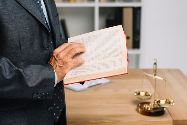 Primo piano del libro di legge della lettura dell'avvocato maturo nell'aula di tribunale Foto Gratuite