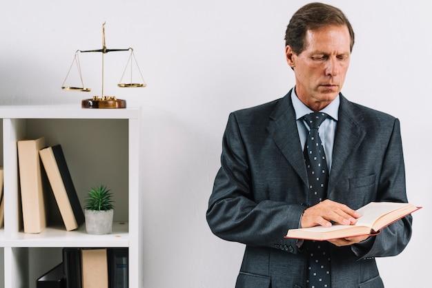 Primo piano del libro di legge della lettura dell'avvocato maturo nell'ufficio Foto Gratuite